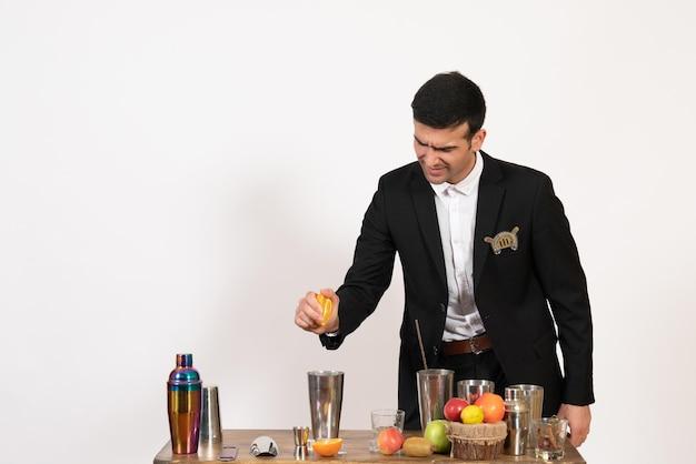 Vooraanzicht mannelijke barman in klassiek pak die een drankje maakt dat oranje op een witte muur knijpt, nachtclub, mannelijke bar, dansdrankje