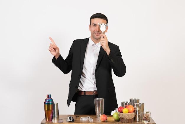 Vooraanzicht mannelijke barman in klassiek pak die een drankje maakt op de witte muur, nachtdrankclub, mannelijke bardans