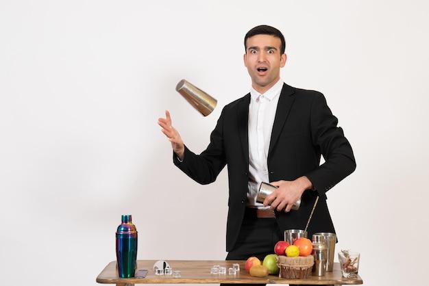 Vooraanzicht mannelijke barman in pak die met shakers werkt en drank maakt op de witte muur, nachtdrankbar, club, mannelijke dans