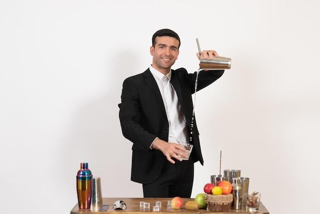 Vooraanzicht mannelijke barman in pak die met shakers werkt en drank maakt op een wit bureau nachtdrank bar club mannelijke dans