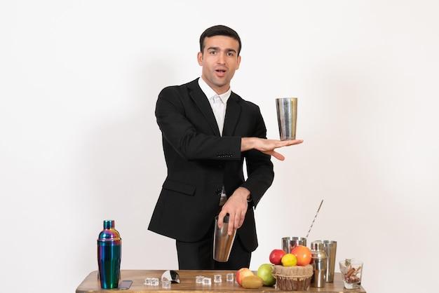 Vooraanzicht mannelijke barman in pak die met shakers werkt en drank maakt op een witte muur, mannelijke dansdrankbarclub in de nacht