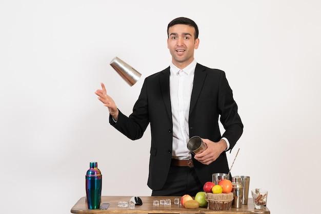 Vooraanzicht mannelijke barman in pak die met shakers werkt en drank maakt op een witte muur, nachtdrankje, mannelijke barclub
