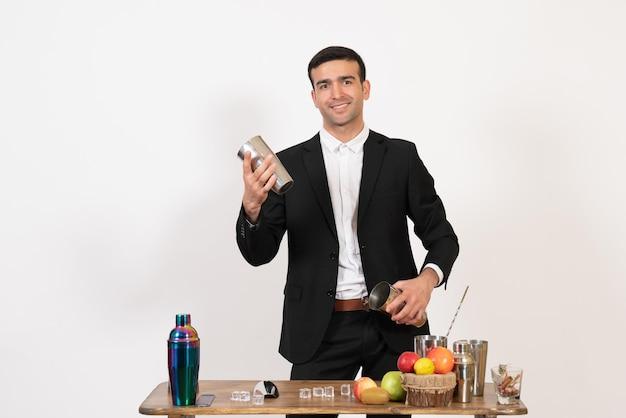 Vooraanzicht mannelijke barman in pak die met shakers werkt en drank maakt op witte bureau nacht mannelijke dansdrank bar club