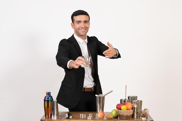 Vooraanzicht mannelijke barman in pak die met shakers werkt en drank maakt op witte muur nacht drankjes bar club mannelijke dans