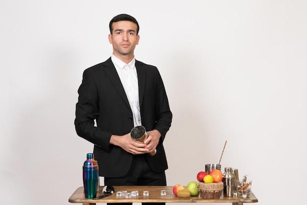 Vooraanzicht mannelijke barman in pak staande voor tafel met shakers en drankjes op witte muur mannelijke bar nachtclub dansdrankje