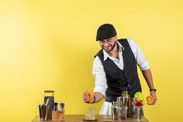 Vooraanzicht mannelijke barman voor barbalie die drank maakt op lichtgele muurbar alcohol nacht jeugddrankclub