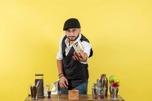 Vooraanzicht mannelijke barman voor tafel met shakers die een drankje bereiden op de gele muurbar alcoholnacht-jeugddrankclub