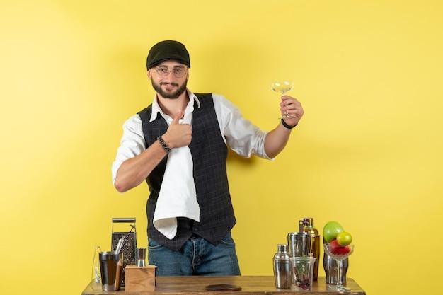 Vooraanzicht mannelijke barman voor tafel met shakers die glazen schoonmaken op gele muurbar alcoholavond jeugddrankclub