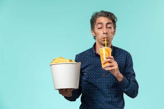 Vooraanzicht mannelijke bedrijf aardappel cips van middelbare leeftijd en frisdrank drinken op een blauwe ondergrond
