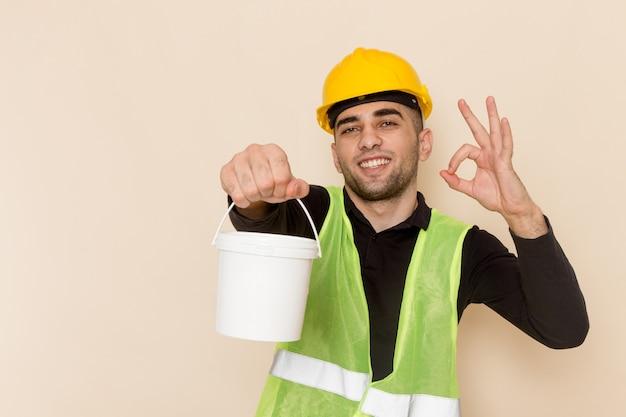Vooraanzicht mannelijke bouwer die in de gele verf van de helmholding op lichtbureau glimlachen