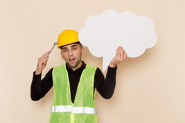 Vooraanzicht mannelijke bouwer die in gele helm groot wit teken op de lichte achtergrond houdt