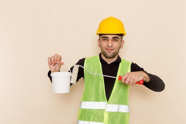 Vooraanzicht mannelijke bouwer in de gele verf van de helmholding en het stellen op lichtbureau