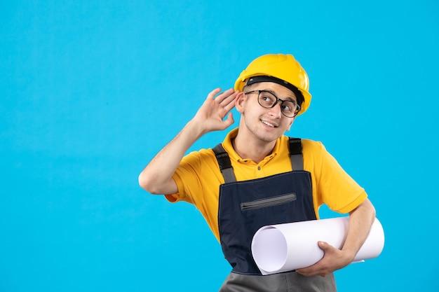 Vooraanzicht mannelijke bouwer in geel uniform met papieren plan op blauw