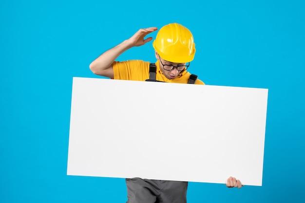 Vooraanzicht mannelijke bouwer in geel uniform met plan op blauw