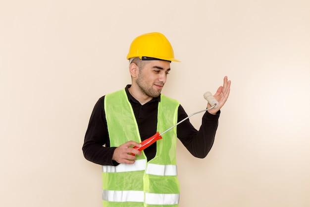 Vooraanzicht mannelijke bouwer in gele de muurborstel van de helmholding op de lichte achtergrond