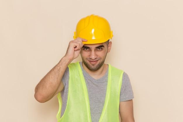 Vooraanzicht mannelijke bouwer in gele helm die eenvoudig op de lichte achtergrond stelt