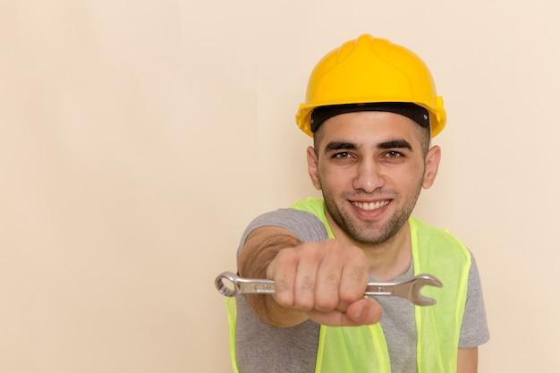 Vooraanzicht mannelijke bouwer in gele helm die zilveren hulpmiddel op de lichte achtergrond houdt