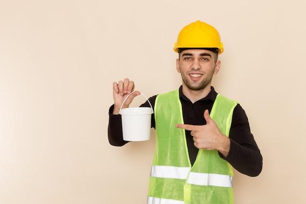 Vooraanzicht mannelijke bouwer in gele helm met verf en poseren op lichte achtergrond