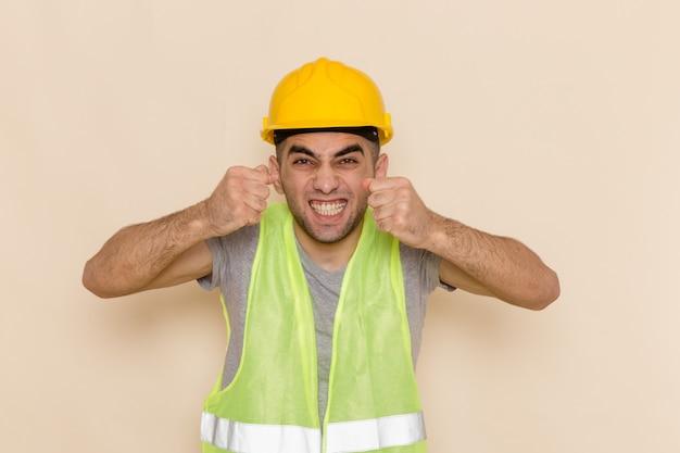Vooraanzicht mannelijke bouwer in gele helm poseren met opgewonden uitdrukking op de lichte achtergrond