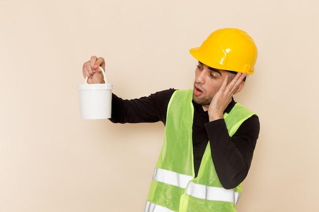 Vooraanzicht mannelijke bouwer in gele helm poseren met verf op de lichte achtergrond