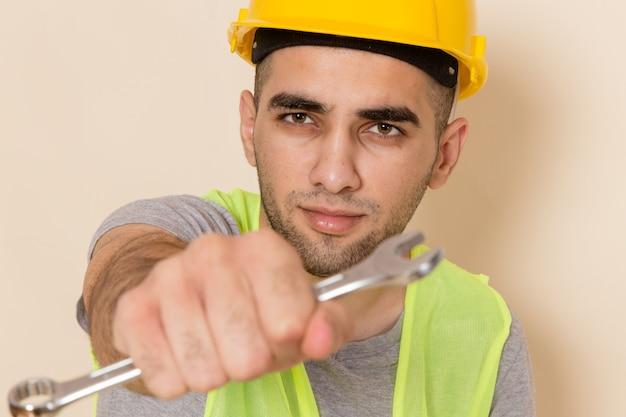 Vooraanzicht mannelijke bouwer in gele helm poseren met zilveren gereedschap op lichte achtergrond