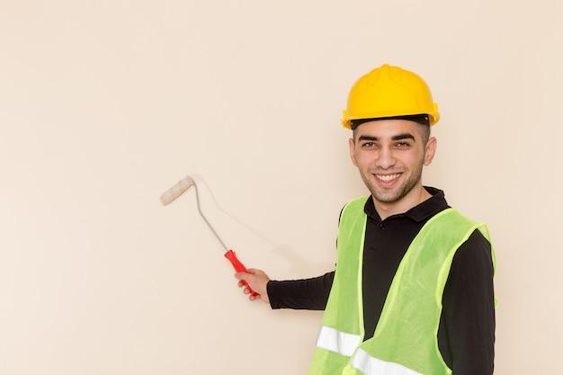 Vooraanzicht mannelijke bouwer in gele helm schilderen muren op de lichte achtergrond