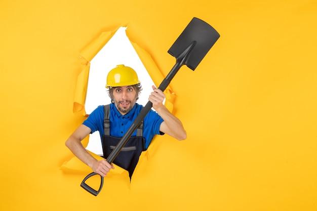 Vooraanzicht mannelijke bouwer in uniform bedrijf schop op gele achtergrond