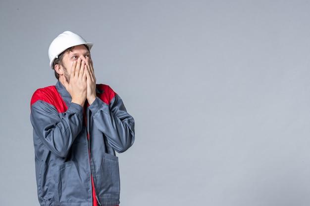 Vooraanzicht mannelijke bouwer in uniform emotioneel op lichte achtergrond