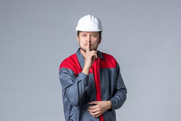 Vooraanzicht mannelijke bouwer in uniform en helm die vraagt om stil te zijn op een grijze achtergrond