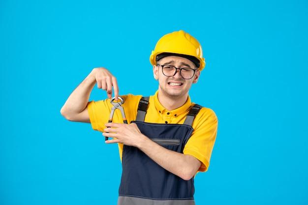Vooraanzicht mannelijke bouwer in uniform en helm die zijn vinger met een tang op blauw snijdt