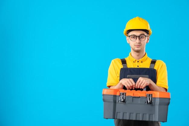 Vooraanzicht mannelijke bouwer in uniform en helm met gereedschapskist op blauw