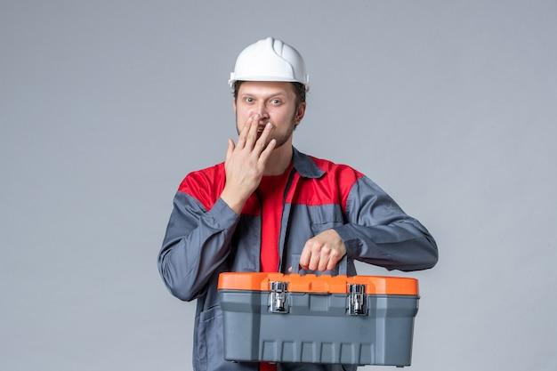 Vooraanzicht mannelijke bouwer in uniform en helm met gereedschapskoffer op grijze achtergrond