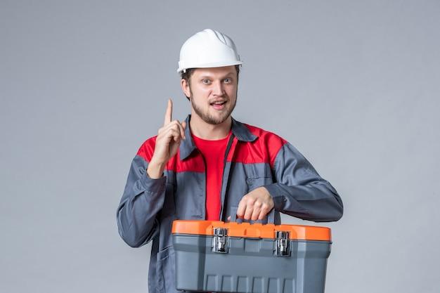 Vooraanzicht mannelijke bouwer in uniform en helm met gereedschapskoffer op grijze achtergrond Gratis Foto