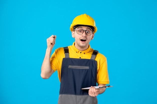 Vooraanzicht mannelijke bouwer in uniform en helm op blauw