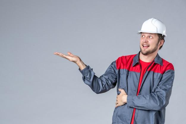 Vooraanzicht mannelijke bouwer in uniform en helm op grijze achtergrond