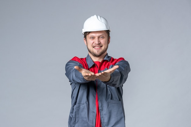 Vooraanzicht mannelijke bouwer in uniform en helm op grijze achtergrond Gratis Foto