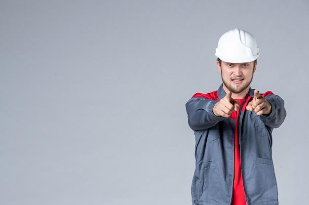Vooraanzicht mannelijke bouwer in uniform en helm op lichte achtergrond