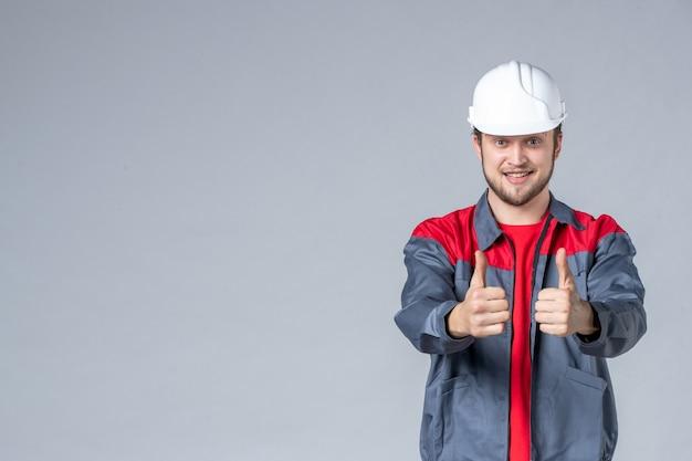 Vooraanzicht mannelijke bouwer in uniform en helm verrukt op lichte achtergrond