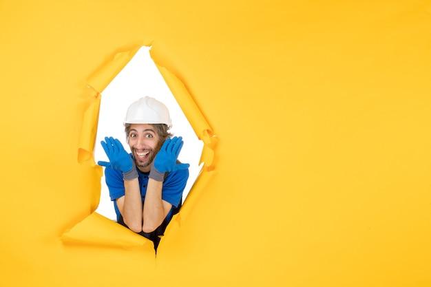 Vooraanzicht mannelijke bouwer in uniform glimlachend op gele muur man bouw baan kleur constructeur architectuur werknemer papier