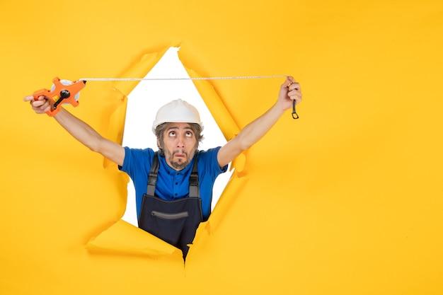 Vooraanzicht mannelijke bouwer in uniform met apparaat op een gele muur werk kleur architectuur bouw werknemer constructeur baan
