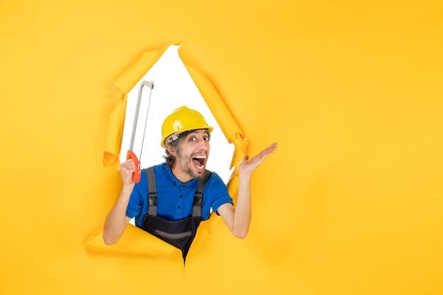 Vooraanzicht mannelijke bouwer in uniform met boogzaag op gele achtergrond
