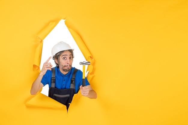 Vooraanzicht mannelijke bouwer in uniform met hamer op de gele muur kleur werknemer baan constructeur architectuur gebouw man