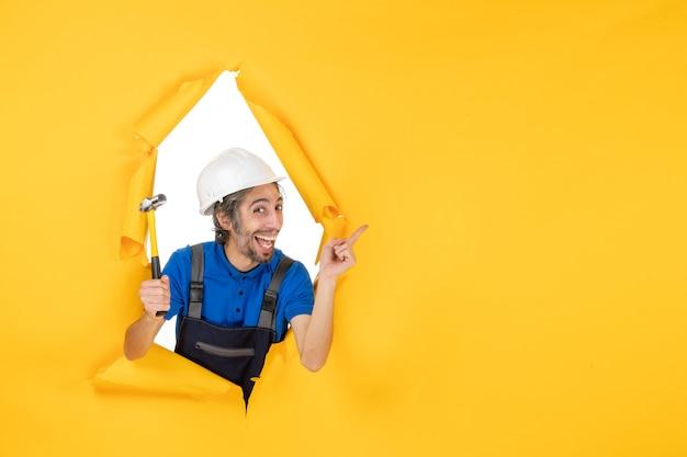 Vooraanzicht mannelijke bouwer in uniform met hamer op de gele muur werknemer man constructor architectuur kleur bouwbaan