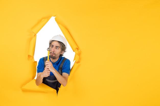 Vooraanzicht mannelijke bouwer in uniform met hamer op gele muur werknemer man bouw baan constructeur architectuur