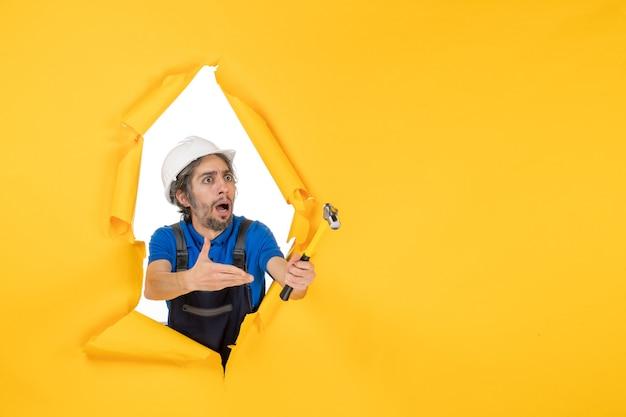 Vooraanzicht mannelijke bouwer in uniform met hamer op gele muur werknemer man bouw constructeur architectuur kleur