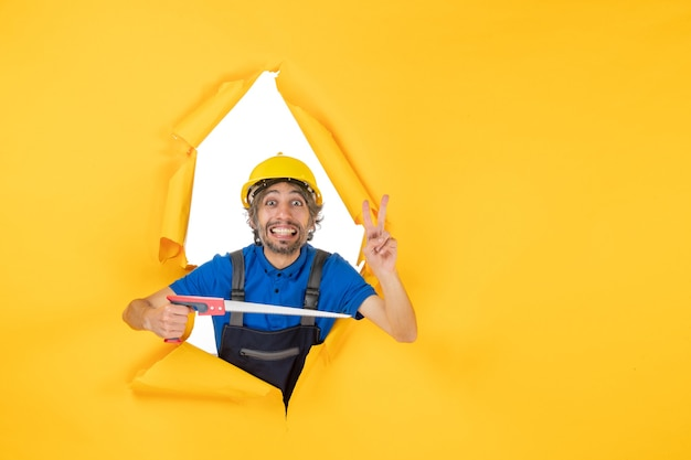 Vooraanzicht mannelijke bouwer in uniform met instrument in zijn handen op een gele muur baan constructeur werk kleur bouwvakker