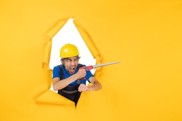 Vooraanzicht mannelijke bouwer in uniform met instrument in zijn handen op gele muur gebouw kleur constructeur werk werknemer baan