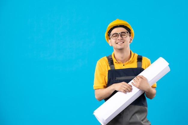 Vooraanzicht mannelijke bouwer in uniform met papieren plan op blauw