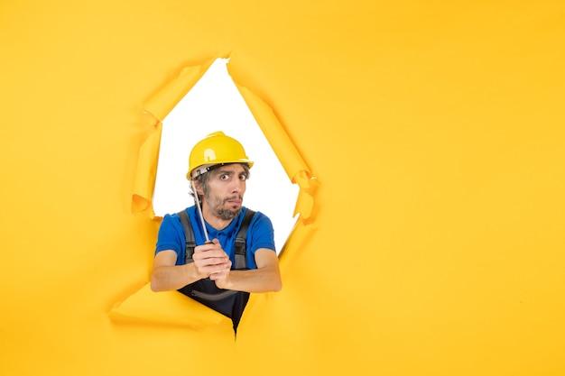 Vooraanzicht mannelijke bouwer in uniform met schroevendraaier op een gele muur aannemer bouwwerk kleur baan werknemer
