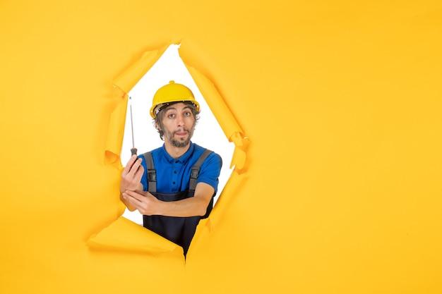 Vooraanzicht mannelijke bouwer in uniform met schroevendraaier op gele muur baan bouwvakker constructeur kleur werk